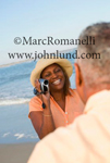 Pic of an African american woman at the beach recording a video of her husband. She is facing the camera, his back is to the camera.
